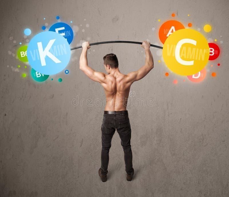 Homem muscular que levanta pesos coloridos da vitamina fotografia de stock royalty free