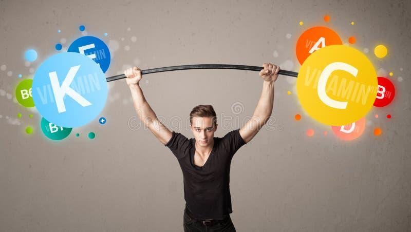 Homem muscular que levanta pesos coloridos da vitamina fotos de stock royalty free