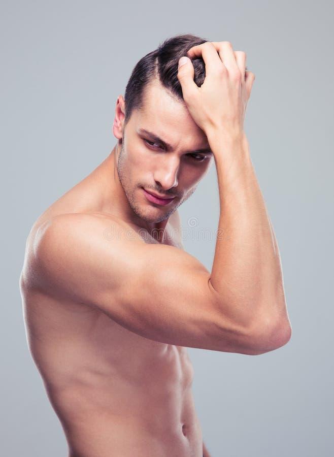 Homem muscular que levanta sobre o fundo cinzento imagem de stock
