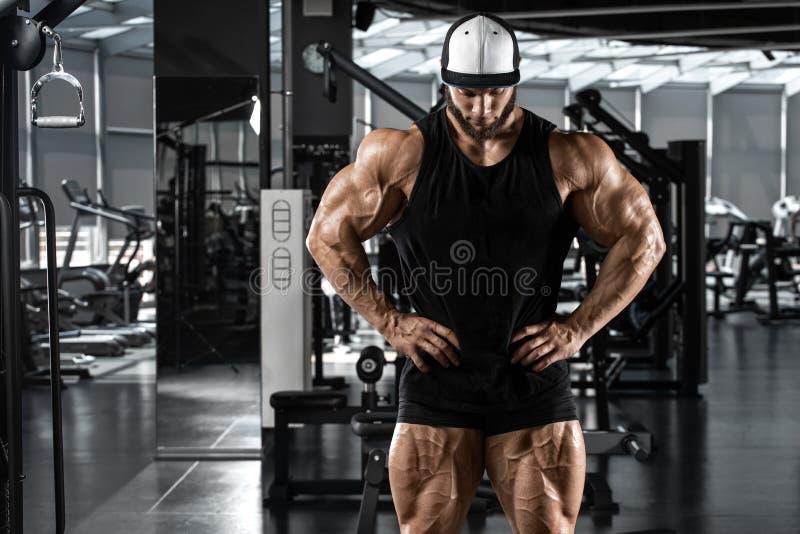 Homem muscular que mostra os músculos no gym, exercício Homem forte do halterofilismo foto de stock