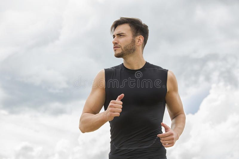 Homem muscular que movimenta-se fora, contexto dramático do céu imagens de stock royalty free