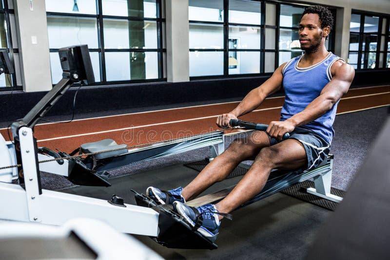 Homem muscular que usa a máquina de enfileiramento imagem de stock