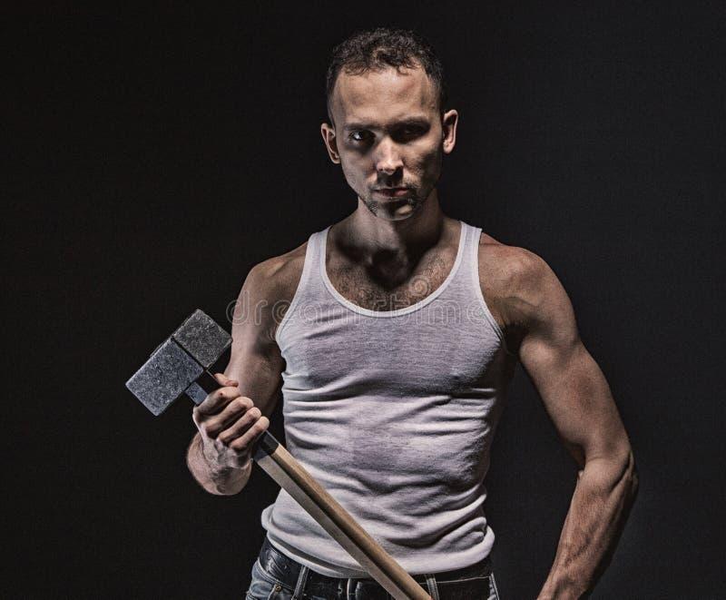 Homem muscular sério com martelo fotografia de stock