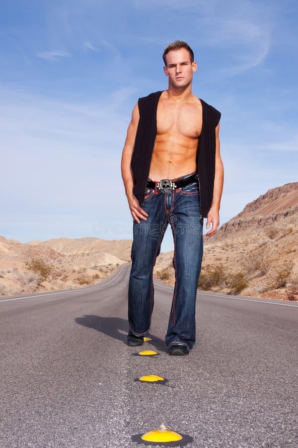 Homem muscular 'sexy' que anda na estrada do deserto imagens de stock