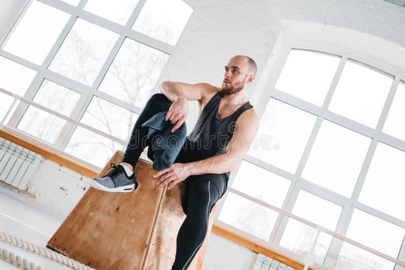 Homem muscular suado cansado que senta-se com a toalha na caixa no gym transversal foto de stock royalty free