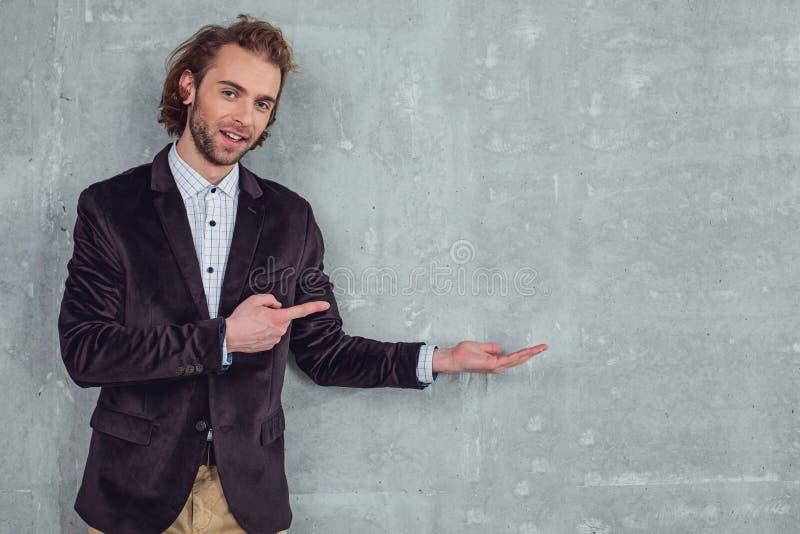 Homem não barbeado alegre que demonstra no espaço vazio foto de stock