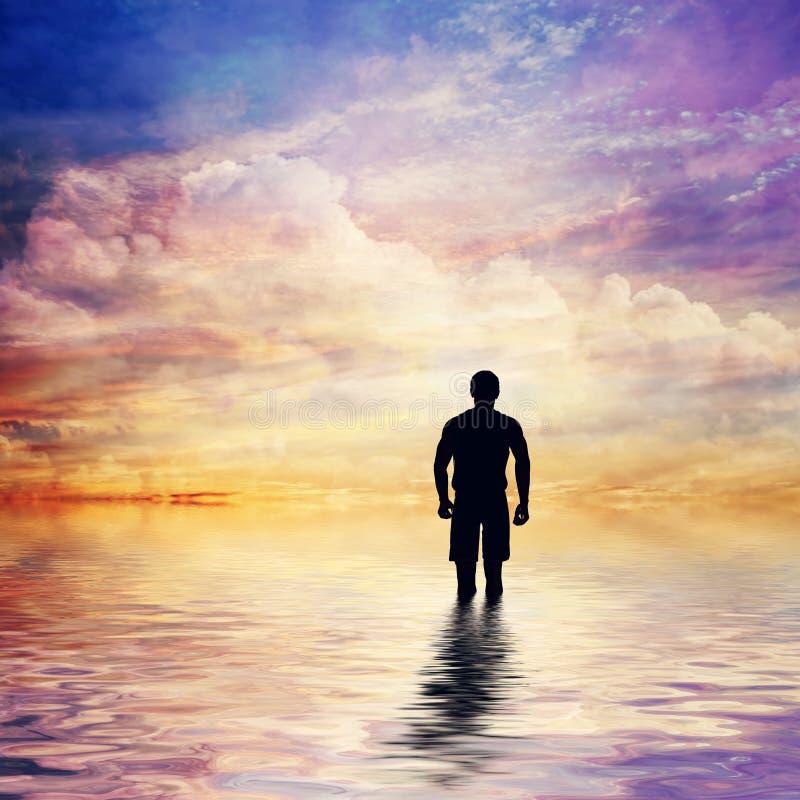 Homem na água do oceano calmo que olha o conto de fadas, céu fantástico do por do sol imagem de stock