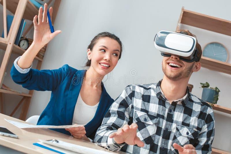 Homem na agência imobiliária real que senta-se na oferta do cliente da exibição do agente dos auriculares da realidade virtual al imagens de stock royalty free