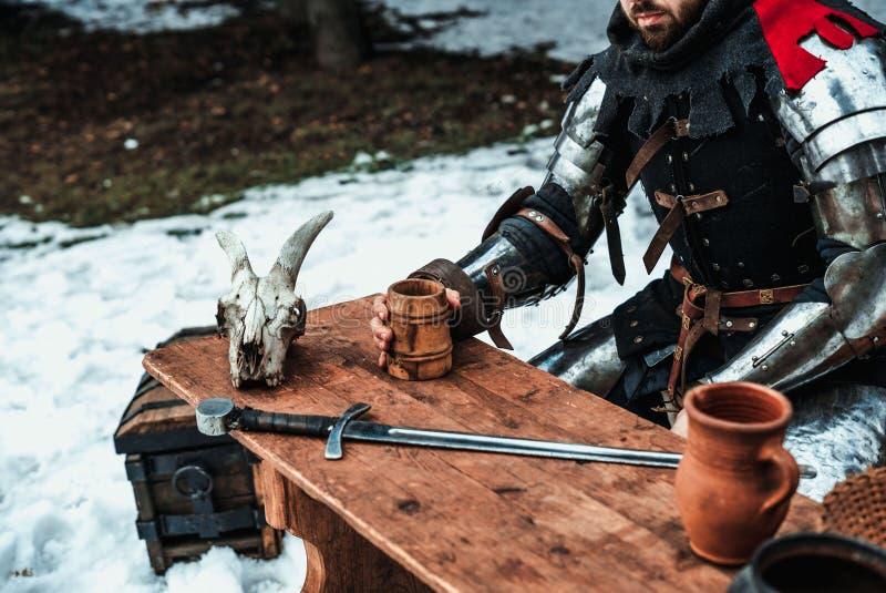 Homem na armadura em uma tabela de madeira imagem de stock