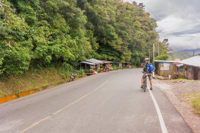 Homem, na bicicleta na estrada em montanhas de Nicarágua imagens de stock
