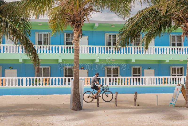 Homem na bicicleta na frente do hotel no calafate de Caye em Belize fotografia de stock royalty free