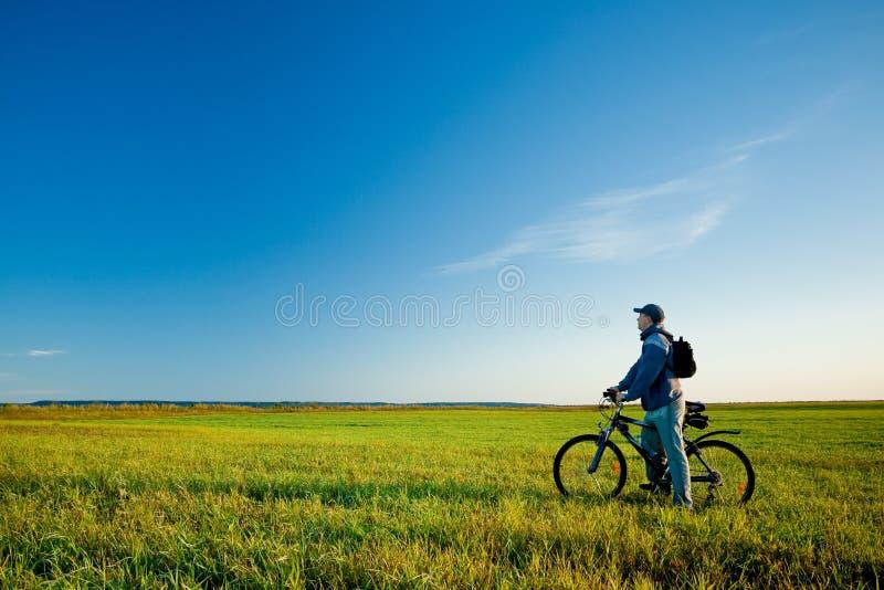 Homem na bicicleta no campo imagens de stock royalty free