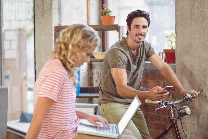 Homem na bicicleta usando o smartphone no escritório fotografia de stock