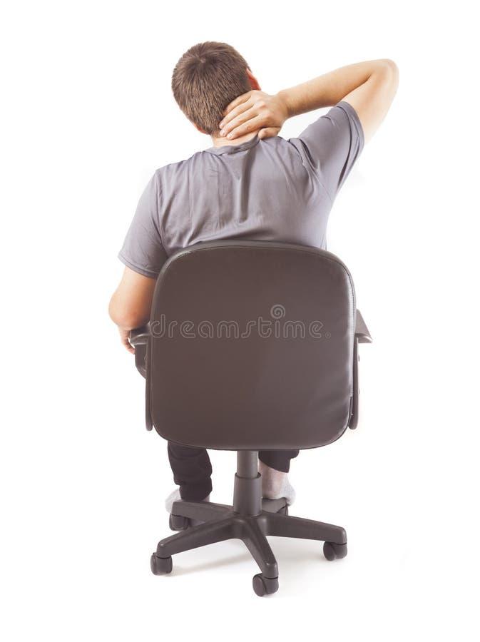 Homem na cadeira com dor de pescoço fotos de stock