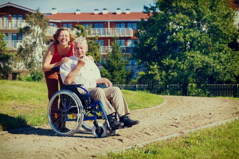 Homem na cadeira de rodas com jovem mulher de sorriso imagem de stock