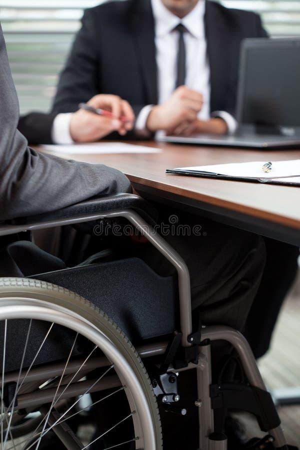 Homem na cadeira de rodas durante a conversação fotografia de stock royalty free