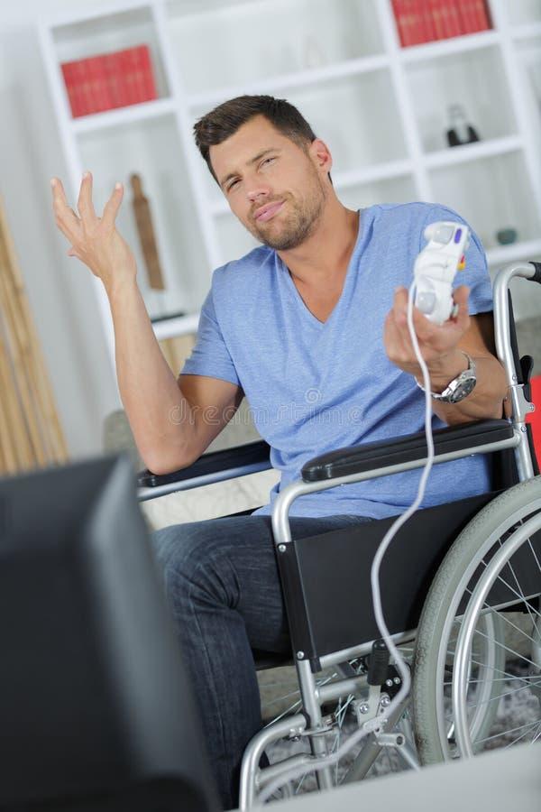 Homem na cadeira de rodas que faz o gesto indiferente imagem de stock