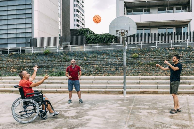 Homem na cadeira de rodas que joga o basquetebol com amigos fotos de stock