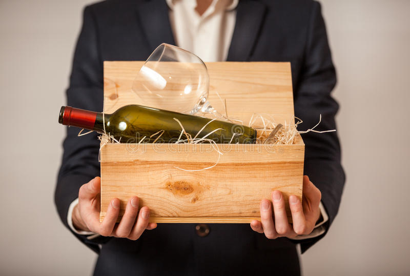Homem na caixa aberta da terra arrendada do revestimento com a garrafa do vinho imagens de stock