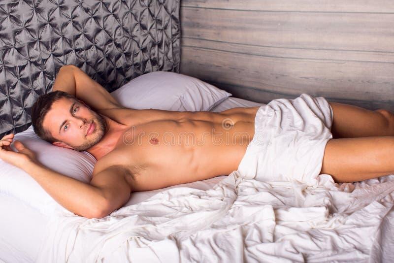 Homem na cama imagem de stock royalty free