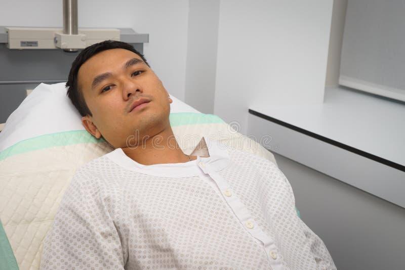 Homem na cama de hospital imagem de stock
