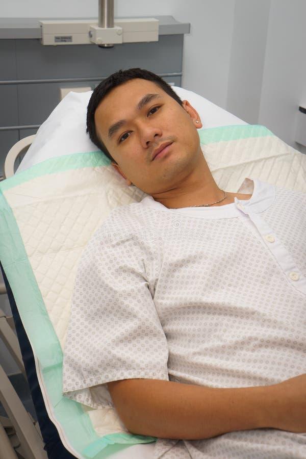 Homem na cama de hospital fotografia de stock