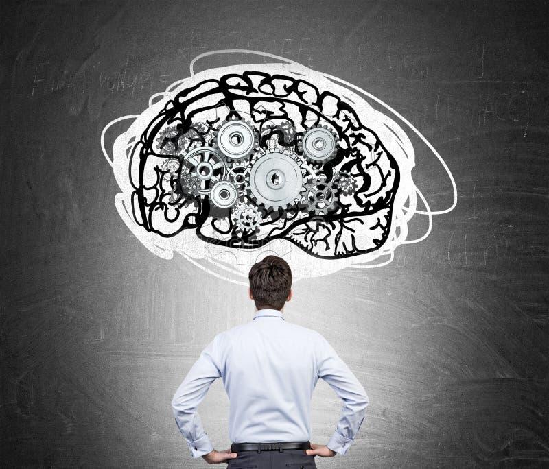 Homem na camisa branca com esboços do cérebro e das engrenagens fotografia de stock