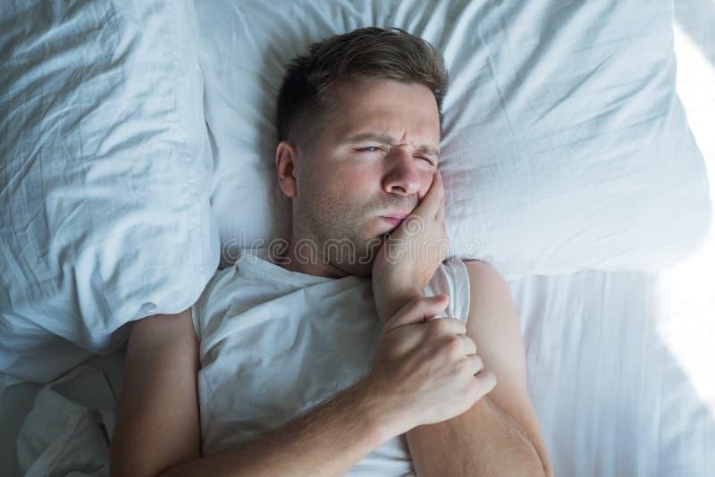 Homem na camisa branca do ` de t que tem a dor de dente e mordente tocante fotografia de stock