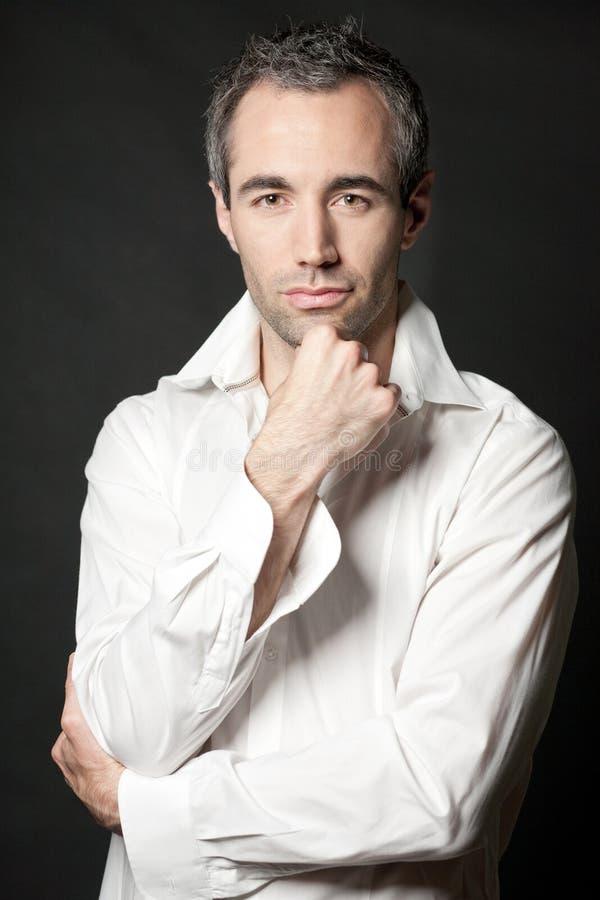 Homem na camisa branca no fundo escuro no estúdio. fotos de stock