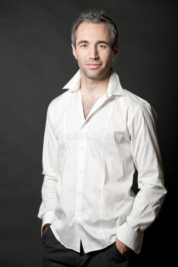 Homem na camisa branca no fundo escuro no estúdio. imagem de stock