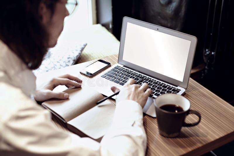 Homem na camisa branca que trabalha no laptop e no café bebendo em um café ou em um co-trabalho Foco no teclado e no telefone imagem de stock royalty free