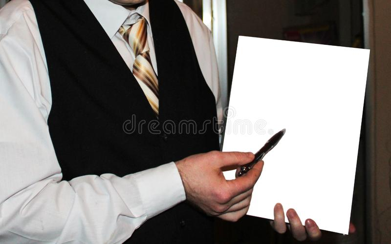 Homem na camisa branca, na veste preta e na gravata listrada dourada guardando o Livro Branco imagem de stock royalty free