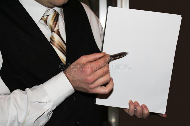 Homem na camisa branca, na veste preta e na gravata listrada dourada guardando o Livro Branco imagens de stock royalty free