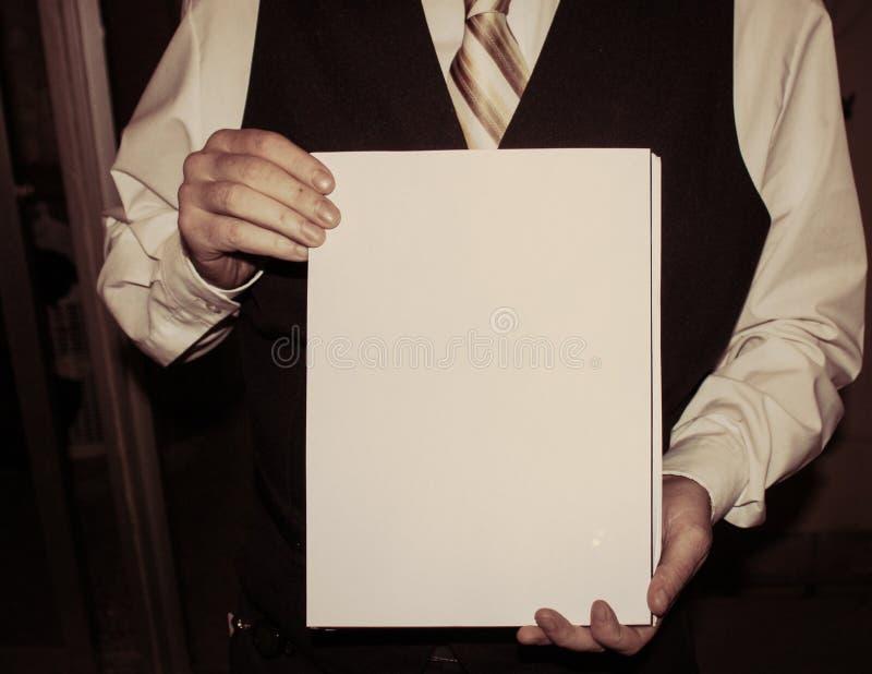 Homem na camisa branca, na veste preta e na gravata listrada dourada guardando o Livro Branco fotos de stock royalty free