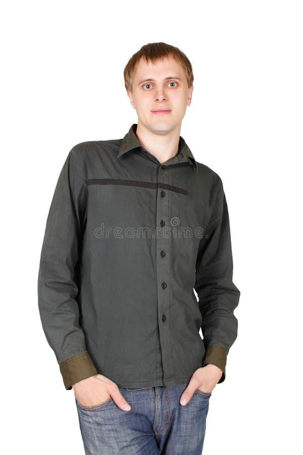 Homem na camisa cinzenta, mãos em uns bolsos, isolados foto de stock