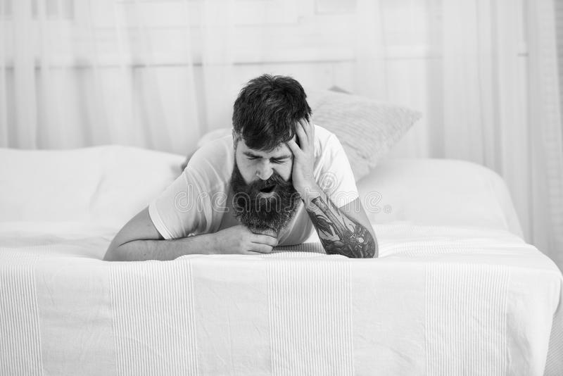 Homem na camisa que coloca na cama acordada, cortina branca no fundo Indivíduo na cara de bocejo que acorda na manhã hangover fotografia de stock royalty free