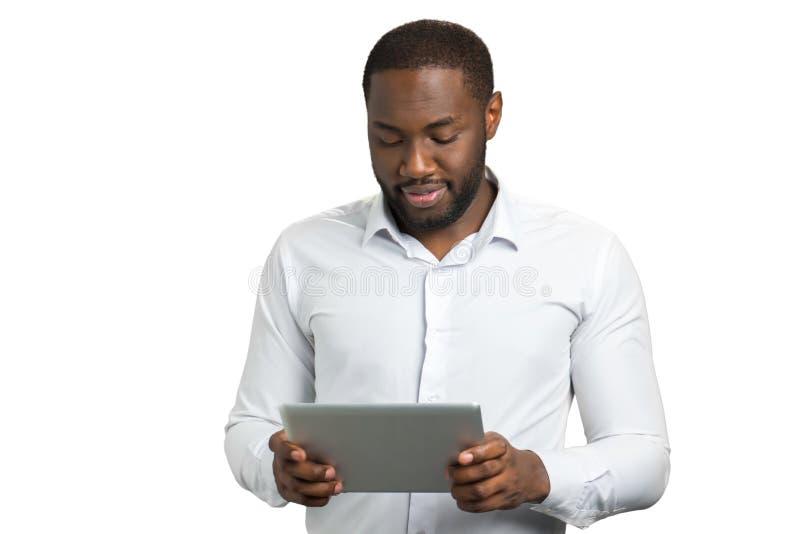 Homem na camisa usando a tabuleta do computador fotografia de stock