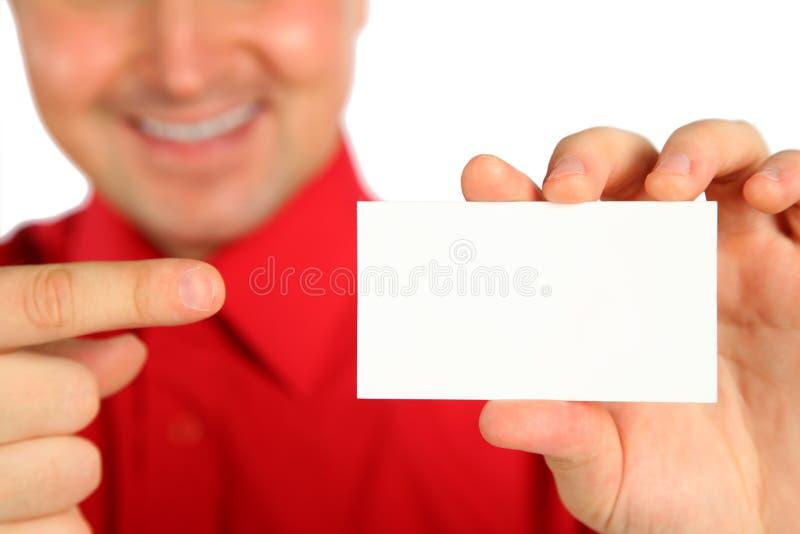 Homem na camisa vermelha com cartão à disposicão imagem de stock