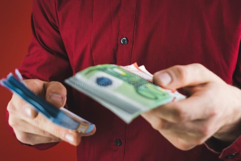 homem na camisa vermelha que guarda pacotes de dinheiro no fundo vermelho fotos de stock