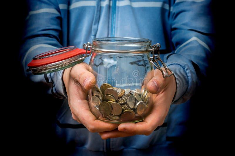 Homem na camiseta azul que guarda o frasco do dinheiro com moedas imagem de stock royalty free