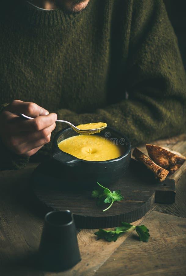 Homem na camiseta escura que come a sopa do milho doce e do camarão fotografia de stock