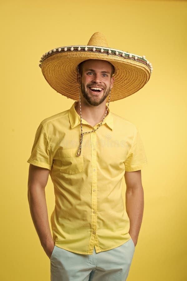 Homem na cara de sorriso que levanta no chapéu do sombreiro com mãos em uns bolsos, fundo amarelo O indivíduo com cerda olha fest imagem de stock royalty free