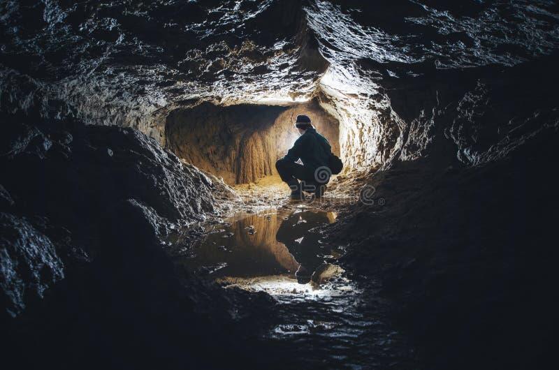 Homem na caverna subterrânea da obscuridade imagens de stock royalty free