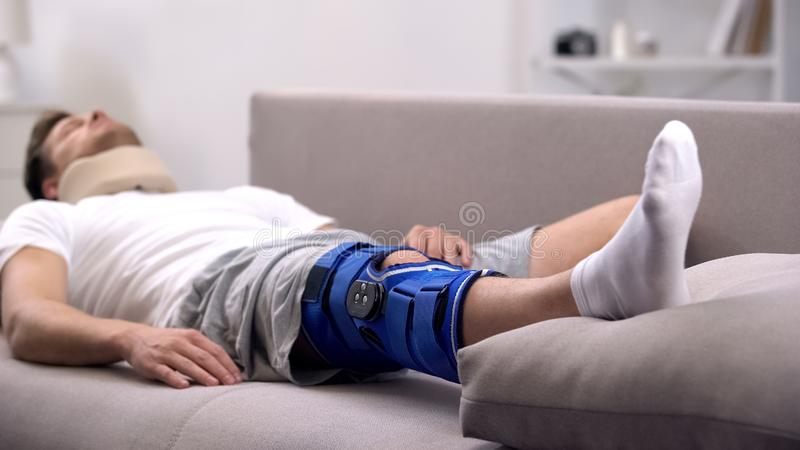 Homem na cinta de joelho cervical do colar e do neopreno da espuma que dorme no sofá, recuperação fotografia de stock royalty free