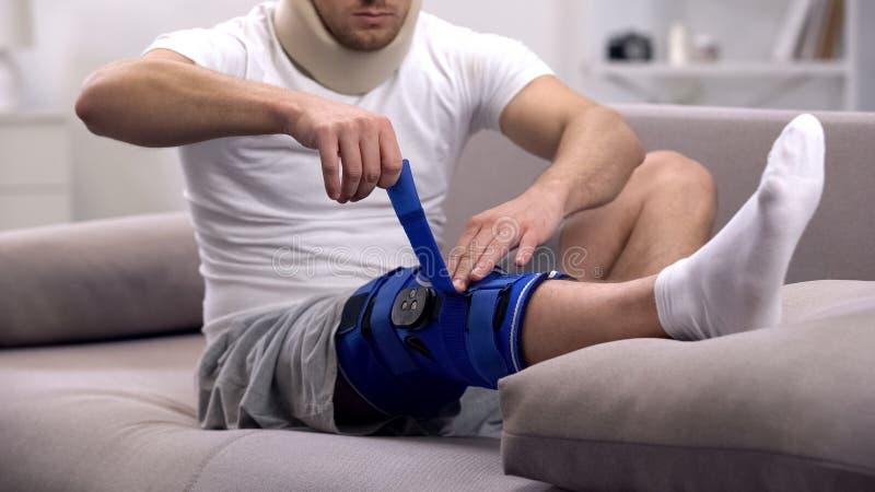 Homem na cinta de joelho de fixação do neopreno do colar cervical da espuma, sentando-se no sofá, reabilitação fotografia de stock royalty free