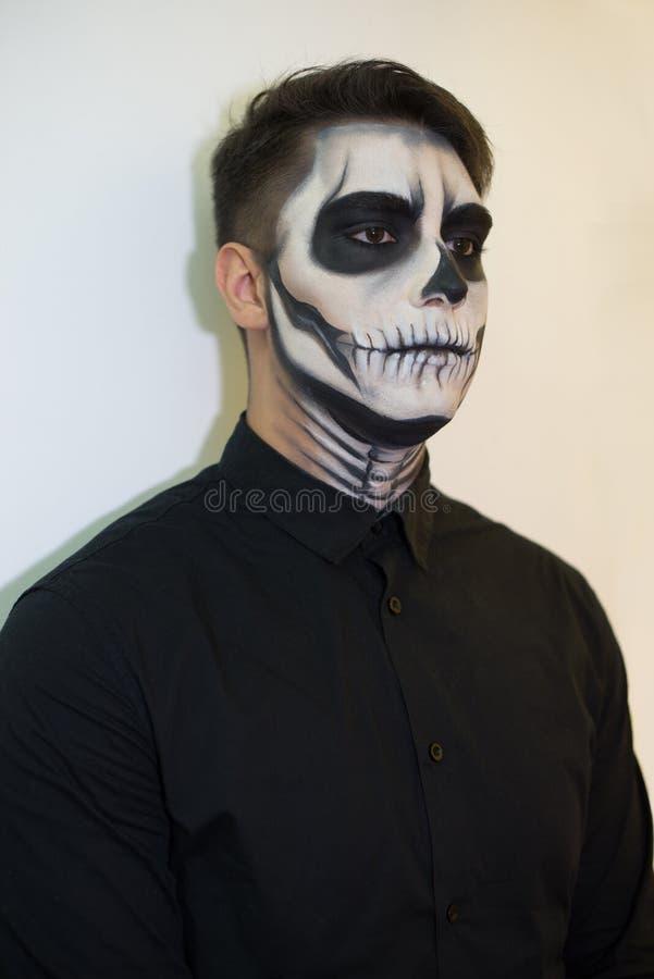Homem na composição Dia das Bruxas tirando um vampiro, esqueleto em sua cara Foto do close-up fotografia de stock royalty free