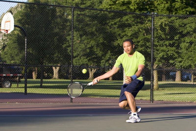 Homem na corte de tênis que joga o tênis - horizontal imagem de stock