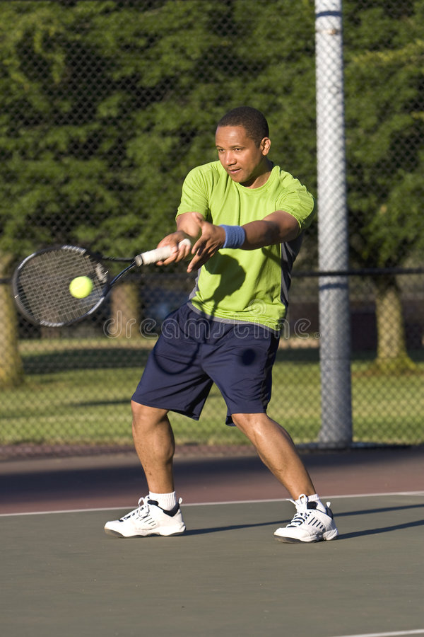 Homem na corte de tênis que joga o tênis - vertical fotografia de stock