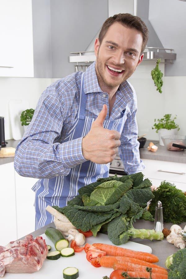 Homem na cozinha com o polegar que prepara acima o jantar imagens de stock