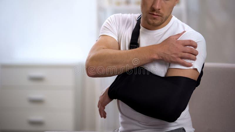 Homem na dor de sofrimento no ombro, resultado do estilingue do braço do traumatismo do trabalho, ortopedia imagens de stock royalty free